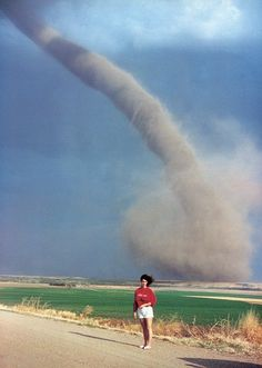 Audra Thomas posing in front of an tornado swirling a mile away from her family farm (in the background). The tornado cut across the farm and destroyed a barn. Photographed south of Beaver City, Nebraska in April 1989 by Audra's mother, Marrilee Thomas. All Nature, Amazing Nature, Science Nature, Strange Weather, Extreme Weather, Tornados, Thunderstorms, Natural Phenomena, Natural Disasters