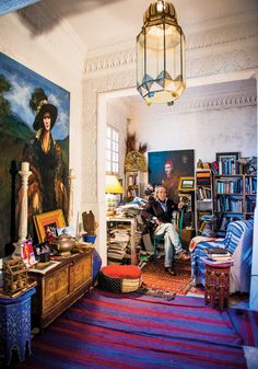 """LAWRENCE AND ANTHEA MYNOTT   The artist and the graphic designer in their """"little chinoiserie salon,"""" with an opaline glass lotus lamp on th..."""