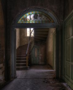 Abandoned in Europe..... stained glass in the arch above the doorway