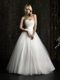 Style No. 8957      A simple and understated design in rich satin and soft tulle. The strapless, satin bodice is slightly scooped, ruched and has a natural waistline. The gown is completed with covered buttons and a tulle A-line skirt.