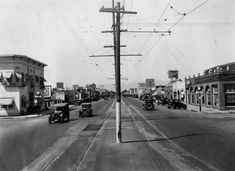 (1926)* - View of Van Nuys Boulevard with Pacific Electric Railway tracks and wires in the middle of the street and cars and shops on the si...