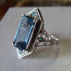 Here is a stunningly lovely Art Deco solid sterling silver Aquamarine and Opal ring. It is size 8.5 . It has nice antique - Deco style detailing with a beautiful lab created 6 ct Aquamarine stone and 4 tiny opal accent stones, 1 on each side and 1 above and below the center stone.. It is hallmarked on the inside 925. The top measures slightly over 1 inch on the top from point to point and narrows to the back. . This ring is simply lovely....it would make an excellent gift for yourself or some...