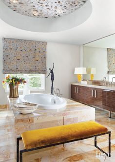 Interior Designer Petra Richards selected gold-toned marble for the floors and tub surround of the master bathroom. The bronze bench, by Paul Ferrante from John Brooks Incorporated, is upholstered with a Bergamo Fabrics silk-velvet. Beside the tub is a Corbin Bronze sculpture from Egg & Dart. Eclectic White Master Bathroom with Gold-Toned Marble Accents