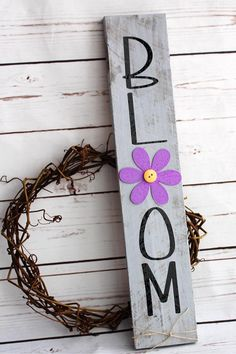 "The perfect spring vertical wood sign to hang in that narrow space you always struggle to find something to fit! Painted in a light gray and had black letters in high quality vinyl. Reads BLOOM"" with one ""O"" being a lavender flower with a yellow button center. Sign is 17 by 3 1/4* and"