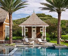 A pool house, chaise lounges, and two perfectly placed palm trees are just inviting a day of leisure.  - Traditional Home ® / Photo: Lucas Allen / Design: Andrew Howard