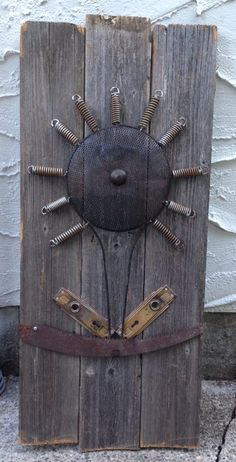Repurposing an old saw blade , door knob plates, bed springs and antique strainer into a rustic piece of garden art