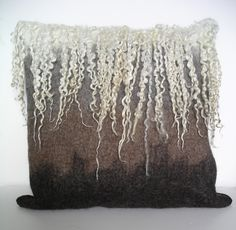 Shetland cushion shaded from natural white through grey, moorit and black. Natural Teeswater locks felted along top edge.