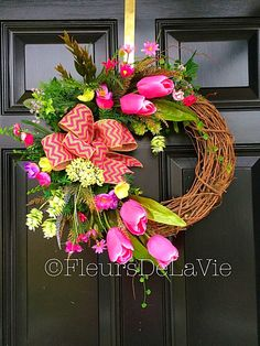 This bright and gorgeous spring wreath is awaiting your front door! Made up on a grapevine wreath with moss, mixed greens, hot pink tulips, light
