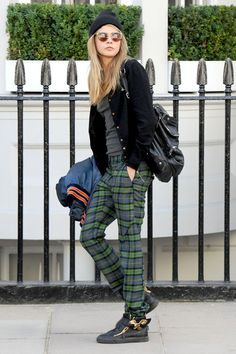 London – August 20 2013  Cara Delevingne wearing Vivienne Westwood trousers with a bomber jacket, sneakers and a beanie hat.