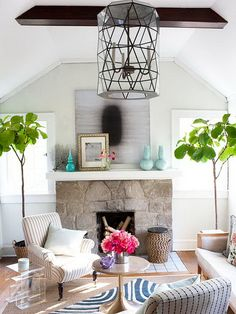 Use your fireplace mantel as a place to showcase your favorite color. Here, a collection of turquoise vases pop against gray artwork and walls. Be bold with layering and position a small piece of art over a large piece