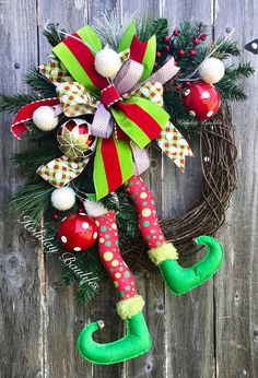 """Super adorable Elf Legs Grapevine Measurements 32"""" Length 23"""" Width Designed on a 18"""" Grapevine Large seven loop bod of 4"""" velvet striped lime green & red, polka dots, solid red velvet with snowdrift edge, and basket woven fun polka dots. Surrounding the bow are evergreen"""