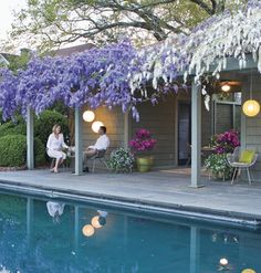 This pool-side patio is especially stunning when its wisteria-covered pergola is in full bloom.