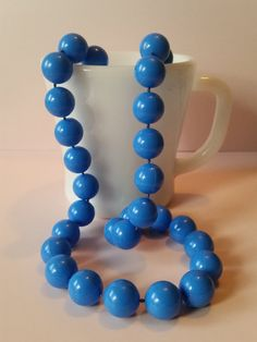 I absolutely adore this cool chunky 1960s mod style necklace! This medium length cerulean blue vintage necklace features large 15mm plastic beads. Slips over head. Necklace is approximately 30 and should fall to sternum on most women.