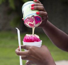Trinidad and Tobago snow cone with syrup and condensed milk.  Isn't the reflection on the can gorgeous?  I love everything about this pic.  Even the way she's holding the straw.  This picture just makes me happy.