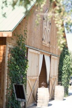 Barn entrance draped with curtains and wine barrels