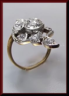 TURN OF THE CENTURY DIAMOND DINNER RING Astoundingly exquisite this platinum and yellow gold turn of the century dinner ring holds 3 old European cut diamond gracefully parading down the center that...