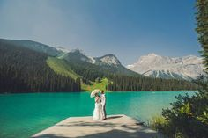 Beautiful Emerald Lake Lodge wedding, bride with parasol overlooking the lake. By Calgary wedding photographer Anna Michalska Photography. See more in the article link!