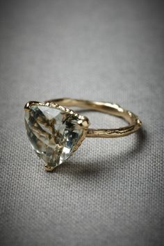 Yellow Gold Woodland Sun Ring   BHLDN  A green amethyst is trillion checkerboard cut, casting dappled light over the golden twig band that cradles it. From Alex Monroe. 18k yellow gold, 12mm amethyst. Handmade in UK.
