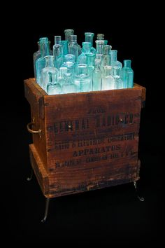 Aqua bottles in wooden crate with up lights.
