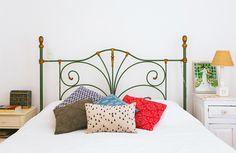 Quarto de casal com cama de ferro  e almofadas coloridas.