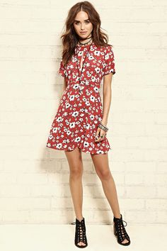 A woven floral print dress with short sleeves, a concealed back zipper, and a keyhole neckline.