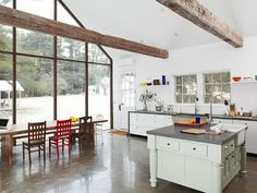 The kitchen's two-story glass wall frames views of the water, gazebo, and barn.