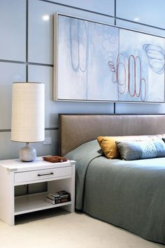Lacquered wall panels add a luxurious feel to this modern master bedroom. The upholstered leather headboard adds a masculine touch, while green bedding and a white nightstand add neutral tones that create a calm, restful feeling.