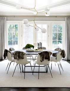 A stunning contemporary design by Tamara Magel. Sheepskin on each chair instead of a cushion. Lindsey Adelman light fixture.