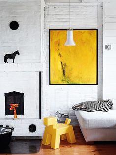 Olohuoneen värit ovat musta, valkoinen ja keltainen. Leiskuva maalaus on paikallisesta osto- ja myyntiliikkestä. Marjaana kehystytti sen mustin kehyslistoin. Eero Aarnion valaisin ja keltainen koira ovat löytöjä outletista. Raidallisen torkkupeitteen Marjaana ompeli itse.