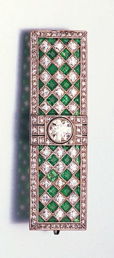 An art deco emerald and diamond plaque brooch, circa 1920 Of chequerboard design, millegrain-set with square and triangular-cut emeralds and French-cut diamonds within a border of smaller single-cut diamonds, with a larger old brilliant-cut diamond to the centre, length 5.2cm., cased.