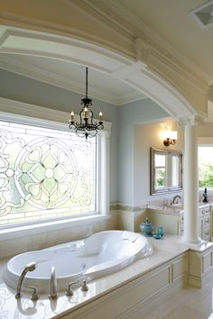 Soaking tub with marble surround stands below a stained glass window, flanked by pillars. Flooring and countertops match the light beige tone throughout.