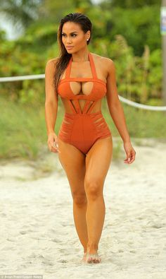 Hot in orange: The 5ft6in beauty was lounging on the beach in an orange cut-out suit...