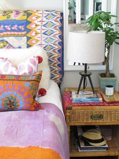 The fun headboard pairs with a fluffy wool pillow, pink ikat pom pom pillow and multi-colored suzani pillow over a pink and orange throw. By Amber Interiors.