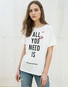Koszulka z wywiniętymi rękawami, pinami i nadrukiem.  Odkryj to i wiele innych ubrań w Bershka w cotygodniowych nowościach