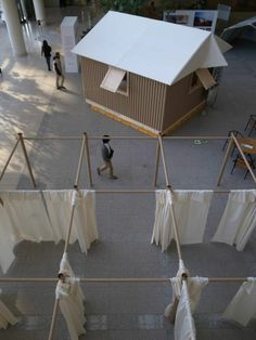 Transitional shelter for refugees made from cardboard tubes and sand-filled beer crates