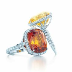 Rings with a 14.32-carat yellow sapphire and a 16.15-carat orange sapphire, both with diamonds in platinum.