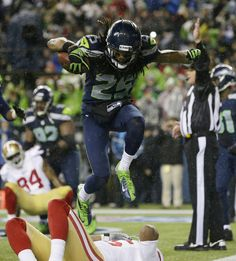 Seattle Seahawks' Richard Sherman jumps over San Francisco 49ers' Michael Crabtree as Sherman celebrates his interception in the second half of an NFL football game, Sunday, Dec. 23, 2012, in Seattle. (AP Photo/Elaine Thompson)