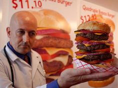 Heart Attack Grill owner Jon poses with a cheeseburger in Chandler, Arizona, in 2009. The restaurant is known for its hospital theme, and diners are made to wear hospital gowns as they eat burgers with names like the triple and quadruple bypass. The Arizona restaurant has since closed and moved to a new location in Las Vegas.
