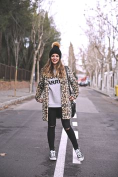 Casual look con abrigo de leopardo, gorro de lana con pompón, converse all star, sudadera gris y vaqueros pitillo negros