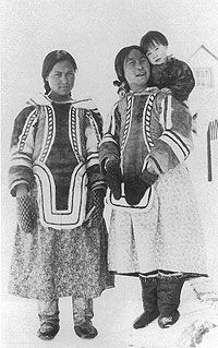 Photograph of Baffinland Inuit women wearing traditional caribou skin amauti and shaved seal skin boots.