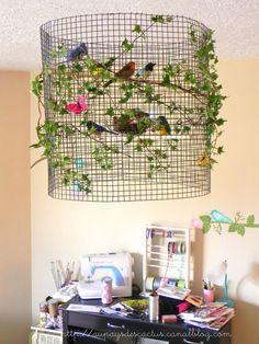 Un lustre fait maison, avec un bout de grillage enroulé sur lui même, quelques branches de lierre, et des petits oiseaux que vous trouverez dans les jardineries.