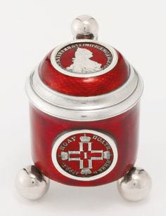 A Russian gilded silver and transparent enamel miniature tankard, St. Petersburg, 1904-1908, the cylindrical body on three ball feet, enameled translucent red over an engine-turned ground, the front inset with a 1799 coin of Paul I, the hinged domed lid with a coin of Catherine II, both on a red guilloché enamel ground, the ball thumbpiece, three ball feet and interior gilded.