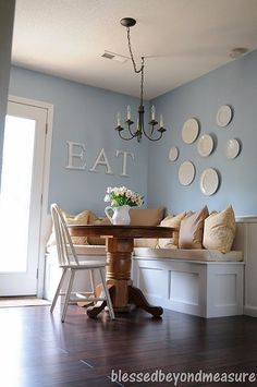 white cream blue dining room banquette padded kitchen bench plate display chandelier