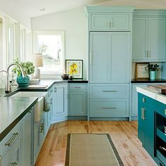 Cool Stock Cabinetry | A deep teal shade of Benjamin Moore's Bermuda Turquoise on the island stands out against the light aqua cabinets in Benjamin Moore's Kensington Green. | SouthernLiving.com