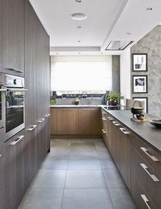Povrch kuchyňské sestavy nábytku je vyrobený z mořeného dubu a podlaha z velkoformátové dlažby imitující beton. I odtud je krásný výhled do zahrady.