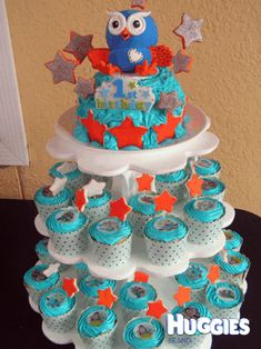 "This cake is a Giggle and Hoot first birthday cake. It is all handmade ... even the Hoot topper!! The top is a giant cupcake butter cake with vanilla icing and handmade stars. On the tiers are beautiful handmade cupcakes again with vanilla icing and handmade stars. My little man absolutely loved it and still to this day says ""My cake"" when he sees a photo of it."