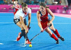 Team USA midfielder Michelle Vittese (R) tries to move the ball while being defended by Germany's Julia Mueller in the Olympic field hockey game.