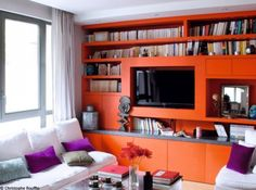 Petit salon bibliotheque orange A remplacer par mur orange + meuble tv orange + tv au mur + tableau ou meubles suspendus orange