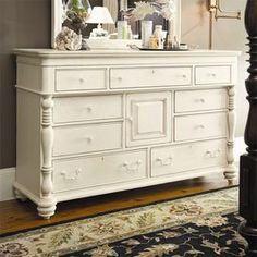"""Nine-drawer dresser with turned pilasters.Product: Dresser    Construction Material: Wood    Color: Linen   Features:  Nine drawers and one raised panel door    Distressed finish accentuates country design    Bottom drawers feature cedar bottoms   Dimensions: 42"""" H x 67"""" W x 21"""" D"""