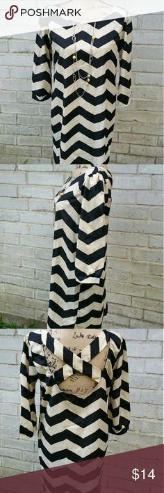 """Boutique Cream &Black Chevron Tunic Fall Fashion Boutique Cream and Black Chevron print quarter sleeve tunic. Or mini dress. Perfect to wear with leggings. Criss Cross syle back design. Excellent condition. Size Large.  Measurements : Length 34"""" 18"""" across front laying flat  #ravenkittystyle #cream #black #chevron #tunic #fall #fallfashion #pairwithskinnies #pairwithlegging #large #boutique #professional #layer #backtoschool Tops Tunics"""